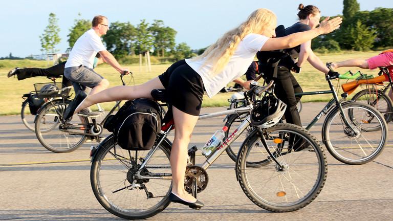 """Eine Frau macht die Yoga-Asana """"der Krieger"""" auf dem Fahrrad"""