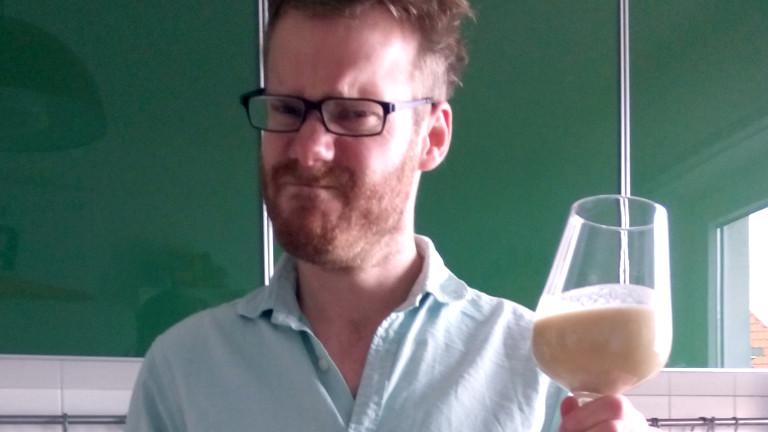 Christian Schmitt verzieht das Gesicht, in seiner Hand ein Glas mit Soylent.