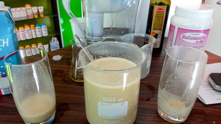 In der Mitte eine braune Mixtur, daneben zwei Gläser.