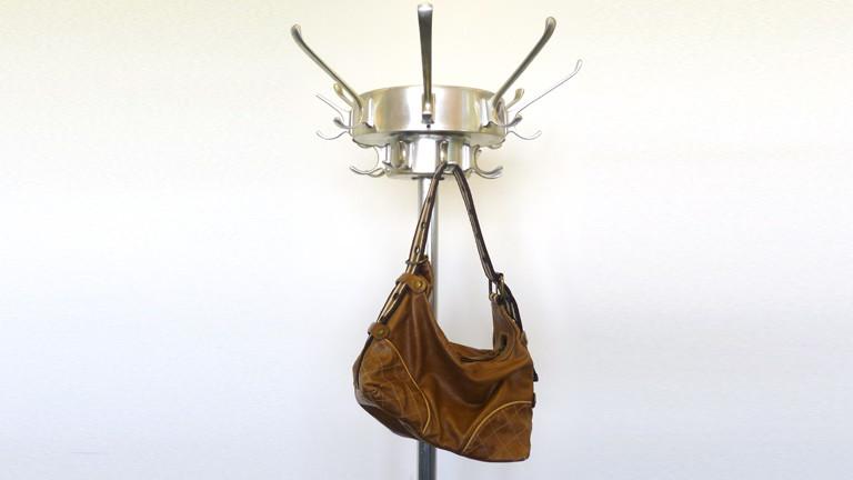 Eine Handtasche hängt an einem Kleiderständer.