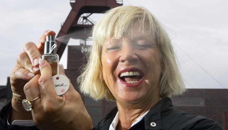 Portrait von Sissel Tolaas mit einem Duft-Zerstäuber in der Hand