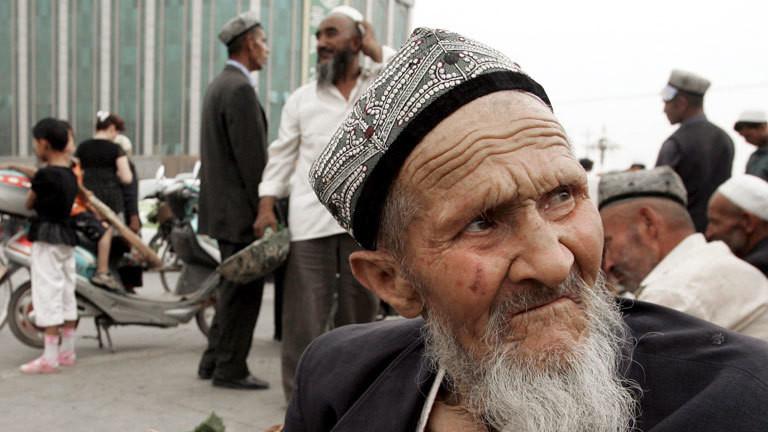 Ein älterer Mann mit Bart sitzt in Kashgar, Xinjiang, am Straßenrand.