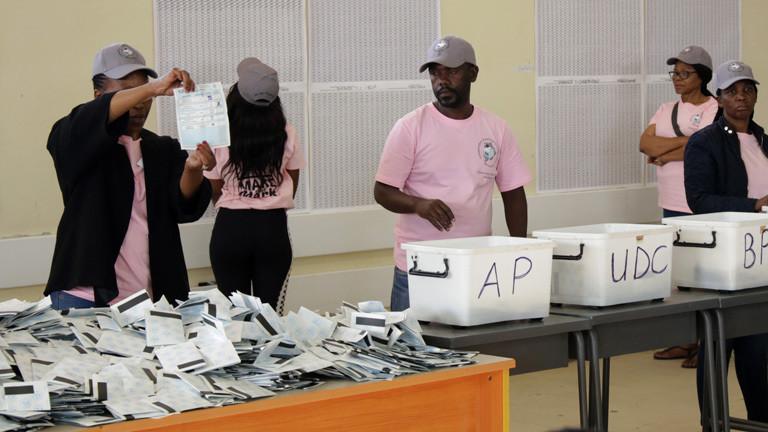 Wahlhelfer zählen Wahlzettel an einem Tisch aus.