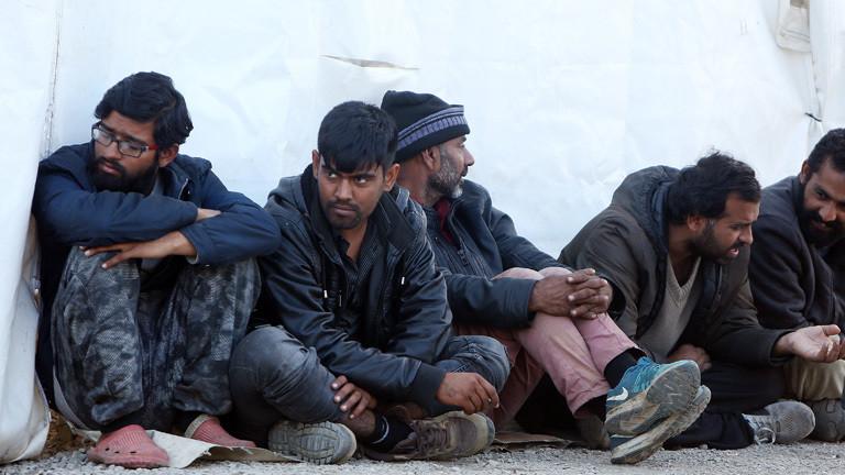 Flüchtlinge sitzen vor weißem Zelt auf dem Boden