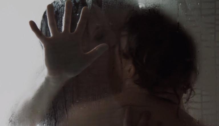 Filmstill aus einem Porno für Frauen: Ein Paar küsst sich an eine Glasscheibe gelehnt.
