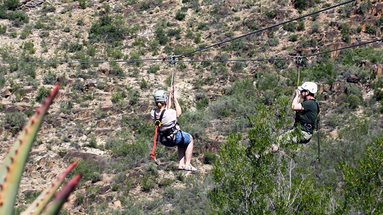 Marcel und Raphaela Franke überqueren eine Schlucht in Südafrika am Oudtshoorn mit einer Zipline.