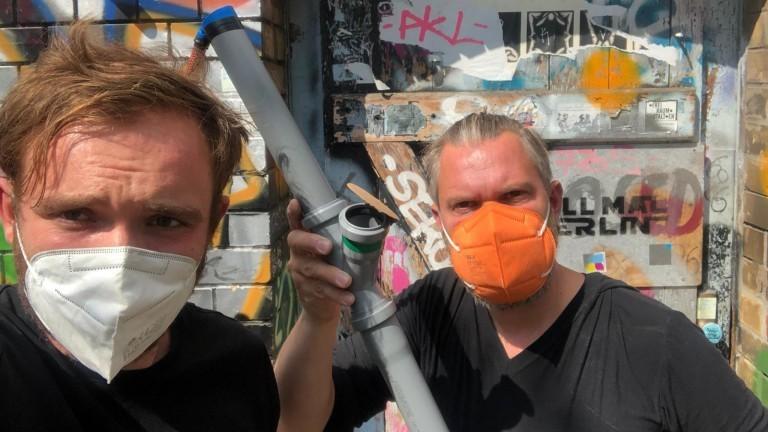 Zwei Männer mit Masken und einem Rohr in der Hand