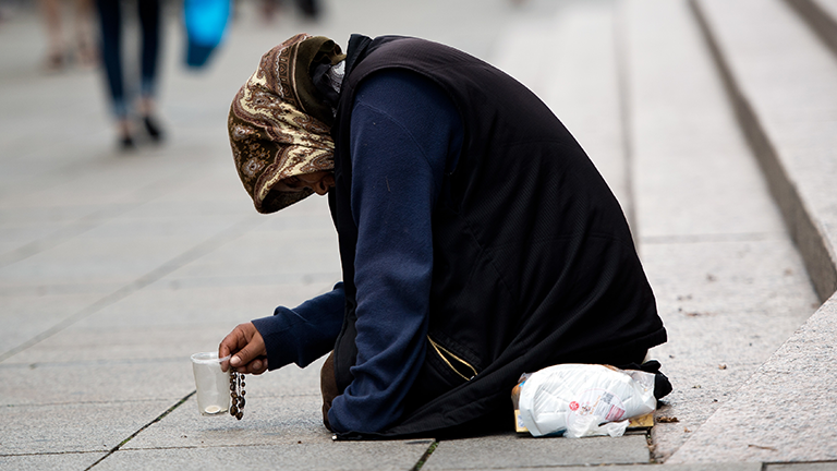 Eine Frau sitzt mit einem Becher in der Hand in der Fußgängerzone und bettelt um Geld