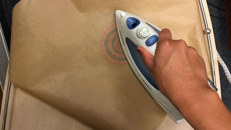 Ein Bügeleisen bügelt über ein Bügelperlenkreis, der von Backpapier geschützt ist