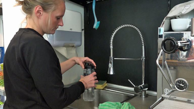 Daria Jung füllt Wasser in eine Flasche