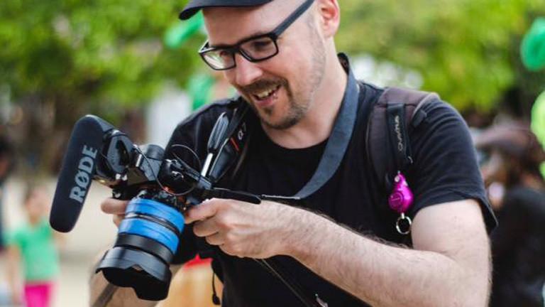 Dennis Klein blickt auf seine Kamera.