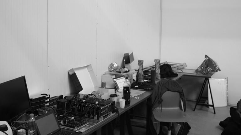 Ein Schreibtisch mit Computern und Gerümpel.