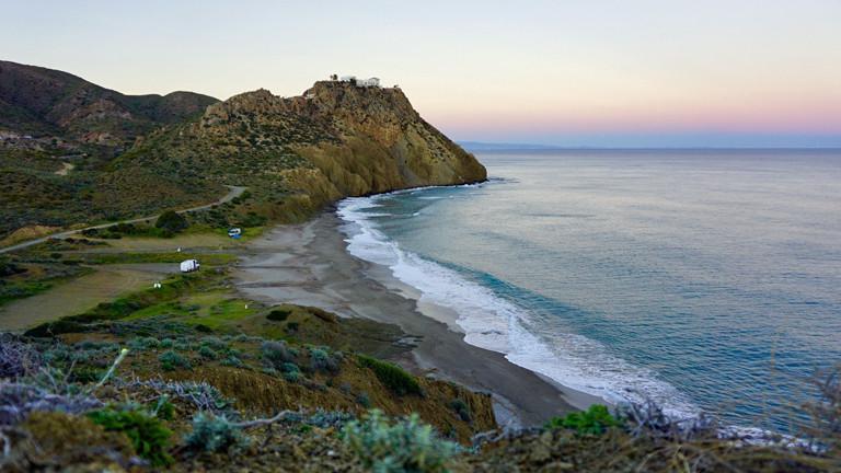 Ein weißer Camper steht klein und verloren in einer malerischen Küstenlandschaft in Spanien