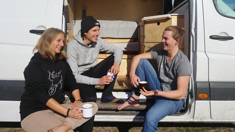 Ina Bierfreund, Felix Hartge und Tim Noetzel trinken Kaffee im Buseingang