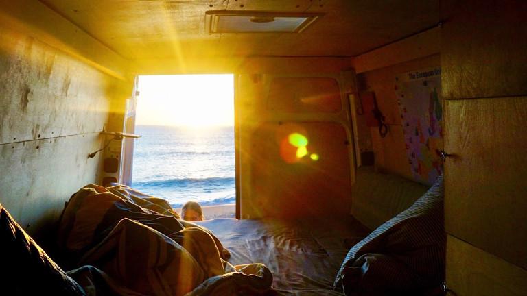 Abendlicht leuchtet vom Meer her in die geöffnete Bustür
