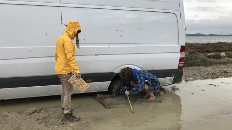 Der Campingbus steckt im Schlamm fest. Ina Bierfreund und ein Helfer versuchen, ihn zu befreien.