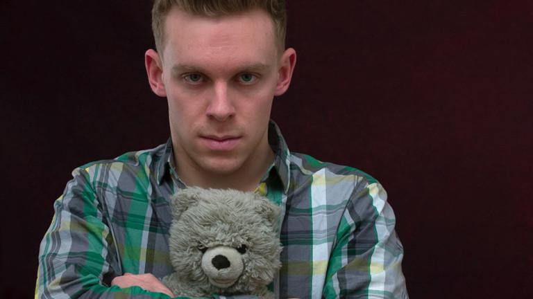 Junger Mann mit Karohemd und grauem Teddybär im Arm.