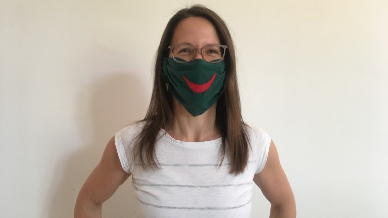 Eine Frau mit einer selbstgerechten Maske lächelt in die Kamera