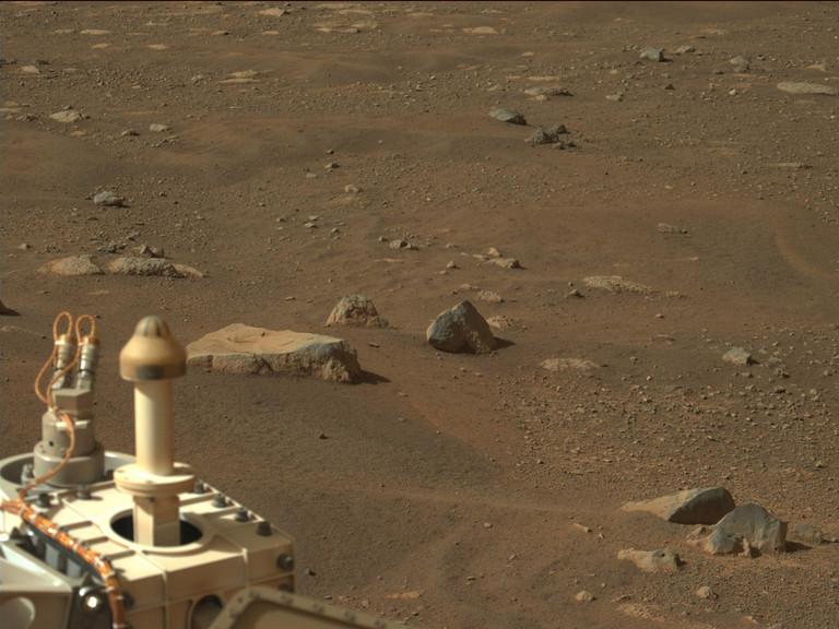 Landschaft auf dem Mars. Im Vordergrund ist ein Teil des Mars Rover Preserverance zu sehen. Im Hintergrund staubiger Boden und einzelne Steine.