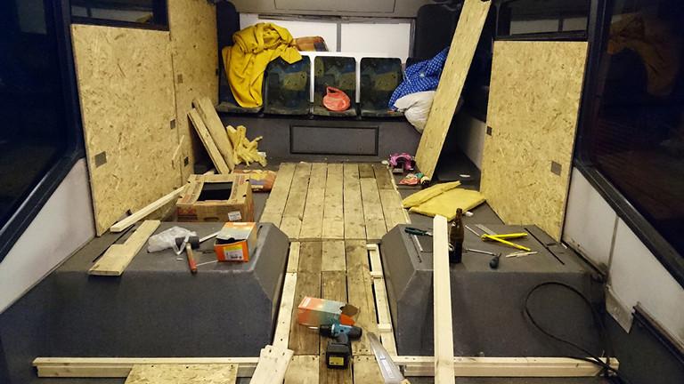 Werkzeug und Spanplatten liegen verteilt im entkernten Bus.