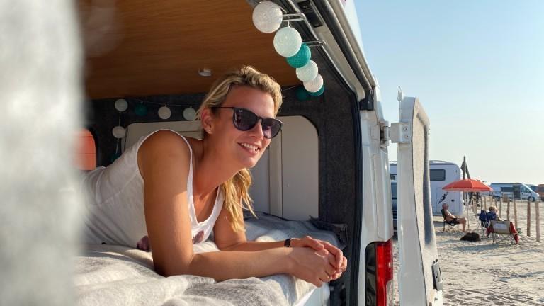 Isa in ihrem Bus am Strand in Sankt Peter Ording.