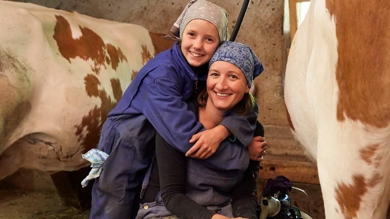 Julia Barbarino und ihre Tochter sitzen zwischen Kühen beim Melken