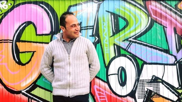 Khalil steht vor einer Graffiti-Wand