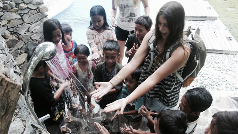 Elisa Bracht spielt zusammen mit Kindern aus dem Dorf unter einer Außendusche.