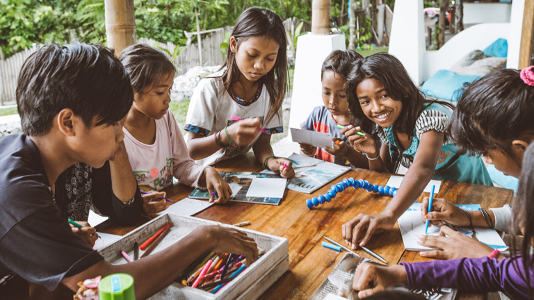 Indonesische Kinder spielen mit Malstiften an einem Tisch.
