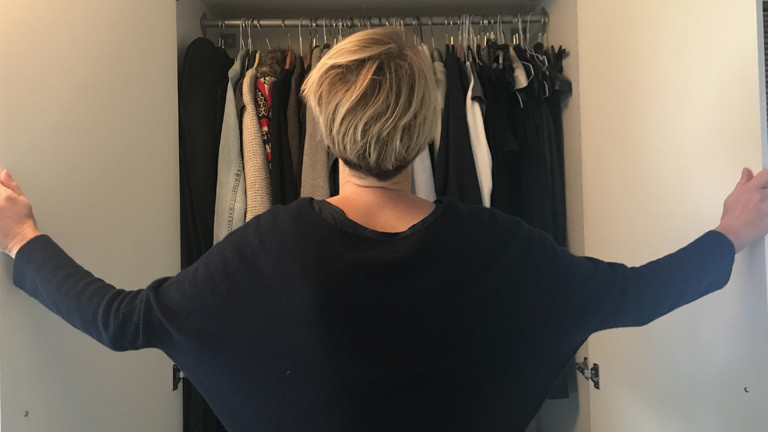 Reporterin steht vor ihrem Kleiderschrank