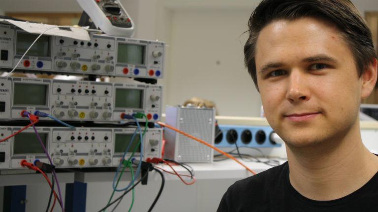 Ein junger Mann vor elektronischen Maschinen.