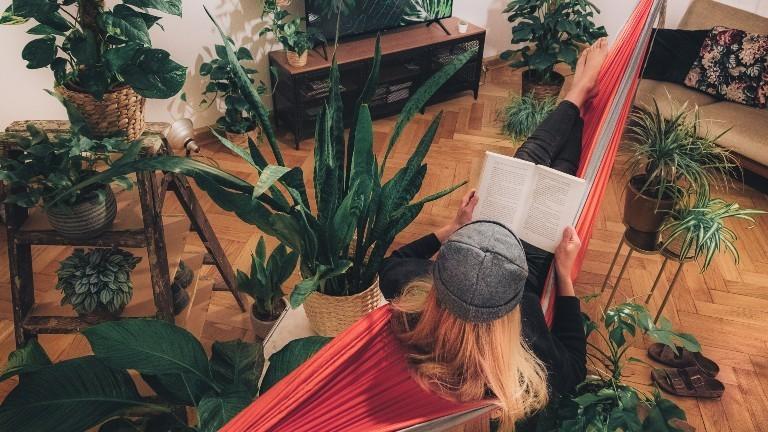 Eine Frau liegt in einer Hängematte im Wohnzimmer