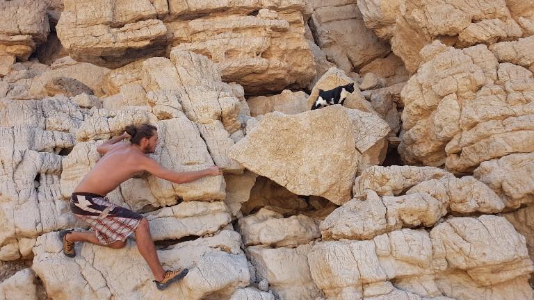 Ein Mann und eine Katze klettern an Felsen entlang