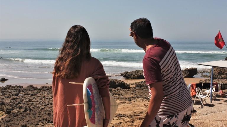 Eine Frau mit Surfboard und ein Mann schauen auf das Meer