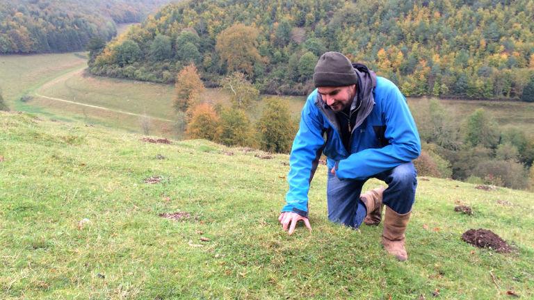Ein Mann in einer Outdoorjacke zeigt auf eine Stelle im Gras.