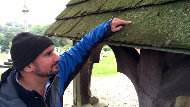Ein Mann in einer Outdoorjacke zeigt auf eine Flechte auf einem Dach.