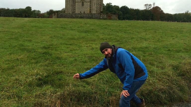 Ein Mann in einer Outdoor-Jacke zeigt auf einen langen Grashalm.