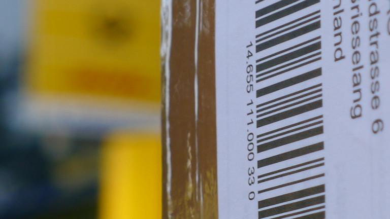 Paketaufkleber und im Hintergrund verschwommen gelb das Schild einer Post.