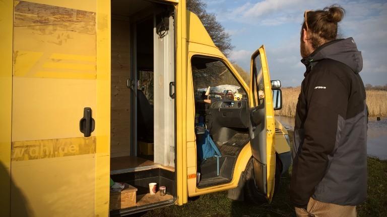 Ein Mann steht vor seinem gelben Wohn-Transporter