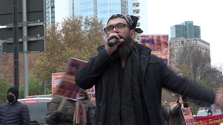 Ein Mann mit Bart und Kopftuch spricht bei einer Demo in ein Mikrofon