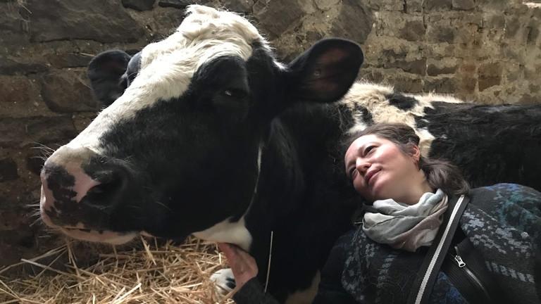 Reporterin Suzan Bazarkaya lehnt an Kuh im Stall