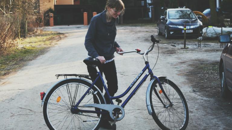 Ein blondes Mädchen schaut auf ein blaues Fahrrad