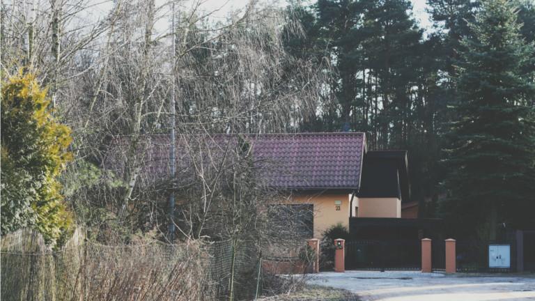 Ein Haus vor dunklen Bäumen.