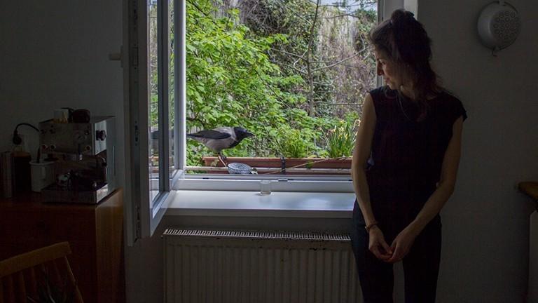 Tabea Hertzog mit einer Krähe an ihrem Küchenfenster.