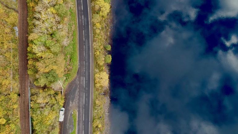 Spiegelnder See und Campingbus von oben, Schottland