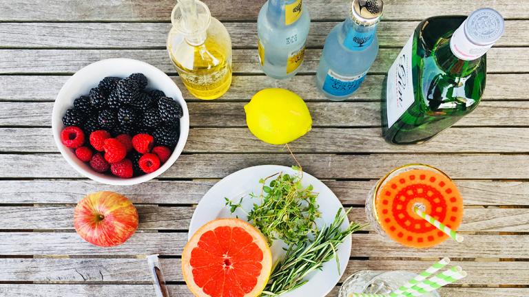 Die Zutaten für einen Gin Tonic mit Grapefruit und Thymiansirup und einen Brombeer-Vanille-Mocktail auf einem Gartentisch