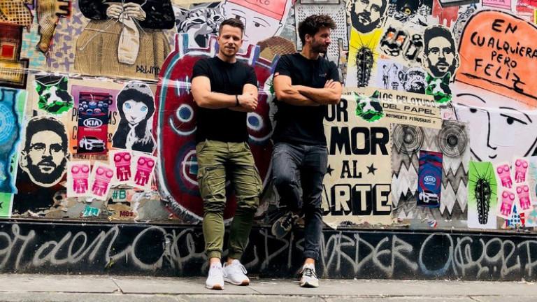 Foto von den zwei Gesprächspartnern Adrian und Christoph, zwei Männern, die vor einer Wand voller bunter Graffiti stehen