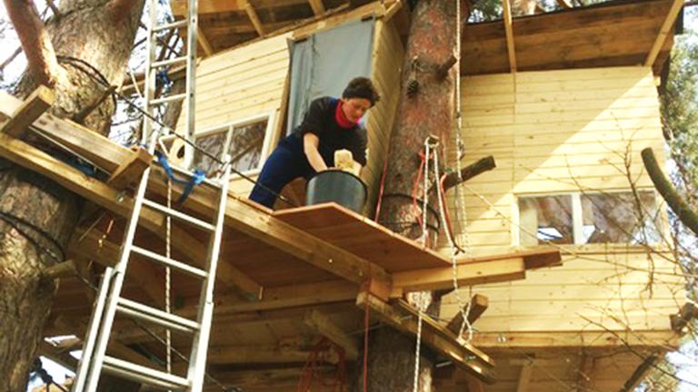 Eine Frau putzt eine Baumhausterrasse