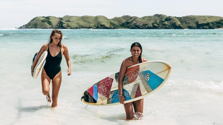 Zwei Frauen mit Surfboards am Strand auf der Insel Lombok