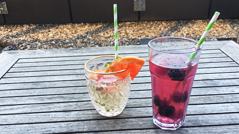 Zwei fertige Drinks auf einem Gartentisch: Gin Tonic mit Grapefruit und Thymiansirup und einen Brombeer-Vanille-Mocktail